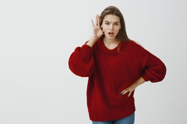 Tell me everything he said to you. indoor shot of shocked and intense charming female coworker in loose red sweater, bending towards camera, holding palm near ear and spreading rumor or gossip
