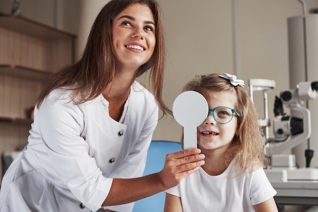 Скажите, что вы видите на доске. маленькая девочка пробует новые синие очки в офтальмологическом кабинете с женщиной-врачом.