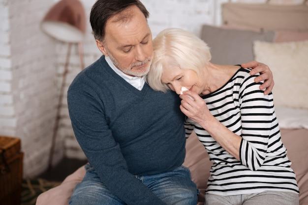 이유를 말해줘. 매우 슬픈 노인 여성이 울고 남편의 어깨에 기대고 있습니다.
