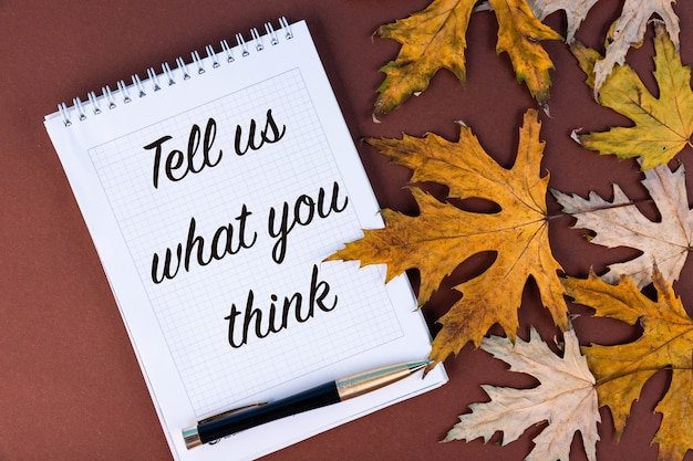 Tell us what you think, inscription, text, in a white notebook, autumn maple leaves. motivation.