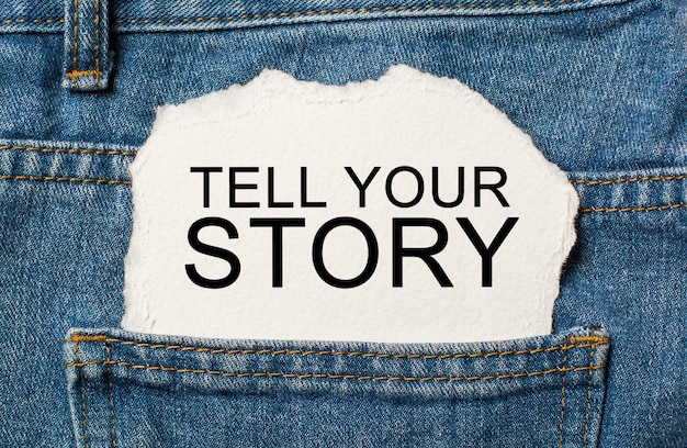 Tell your story on torn paper background on jeans business and finance concept