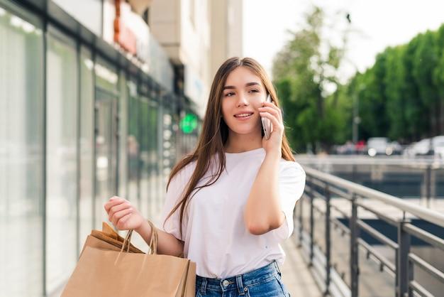 Рассказываю другу о распродажах. красивая молодая улыбающаяся женщина, держащая хозяйственные сумки и говорящая по мобильному телефону, стоя на открытом воздухе
