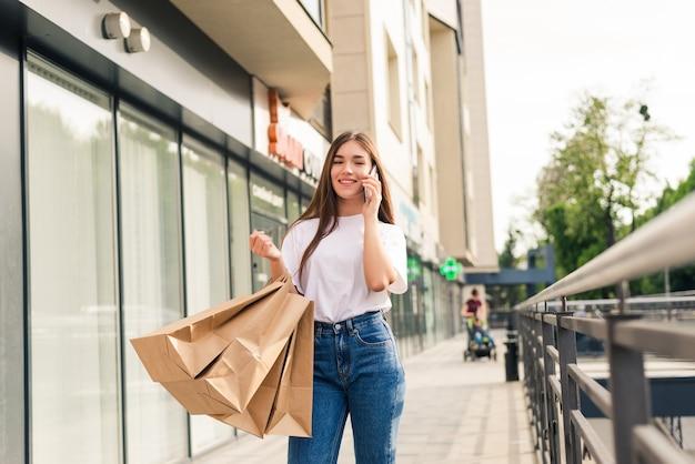 友人に販売について話す。ショッピングバッグを持って、屋外に立っている間携帯電話で話している美しい若い笑顔の女性