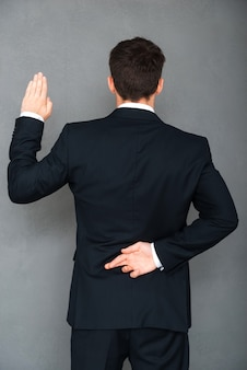 Telling lies. rear view of young businessman keeping his fingers crossed and arm raised while standing against grey background