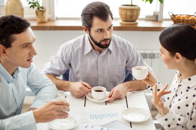 Сообщая новости. красивый довольный бородатый мужчина пьет кофе и смотрит на темноволосую женщину, держащую чашку и говорящую