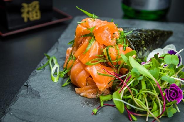 てまき寿司。伝統的な日本料理、上品な雰囲気の中で飾られたプレミアムサーモンテマキ。