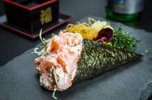 てまき寿司。伝統的な日本料理、上品な雰囲気の中で装飾されたクリームチーズを添えたプレミアムサーモンテマキ。