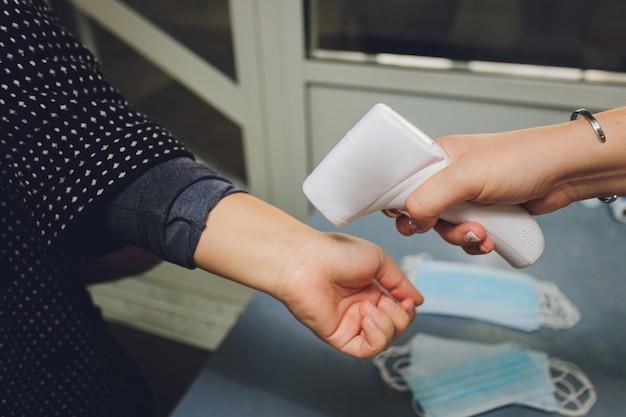 Измерение температуры электронным инфракрасным термометром руки женщины у входа в