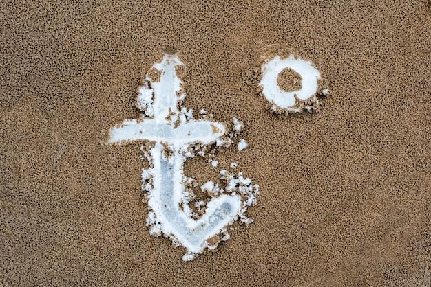 砂に描かれた温度t記号。砂の下には雪があります。春が来た-寒さから暖かいへと気温が変化しました。