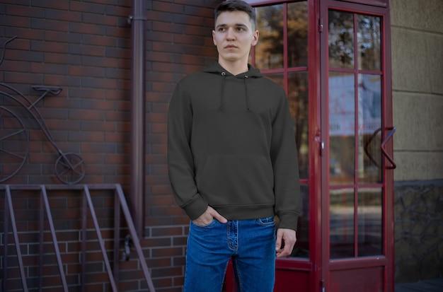 젊은 남자의 템플릿 검은색 후드티, 앞모습, 거리에서 옷을 보여줍니다. 온라인 상점에서 광고하기 위한 빈 남성복 모형. 디자인을 위한 소매가 있는 후드