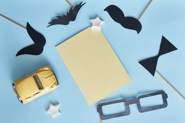 Template for greeting card black paper mustache, glasses and yellow toy car