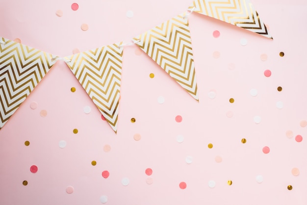 Template for the holidays. paper garland of flags on a pink background with confetti