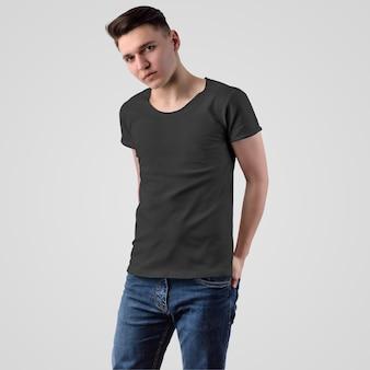 白い背景、正面図に彼のポケットに手を入れたブルージーンズの若い男のテンプレート男性黒tシャツ。デザインとパターンのプレゼンテーションのためのファッショナブルな空の服のモックアップ。