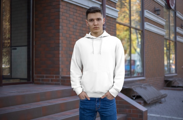 Шаблон мужской белый балахон на парня, вид спереди, презентация одежды на улице. макет вытяжек на фоне кирпичного дома. место для вашего выкройки и дизайна.