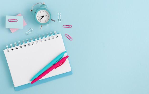 Шаблон макета. рабочая область с ноутбука, часы и ручки на пастельных синем фоне. вид сверху. копировать пространство