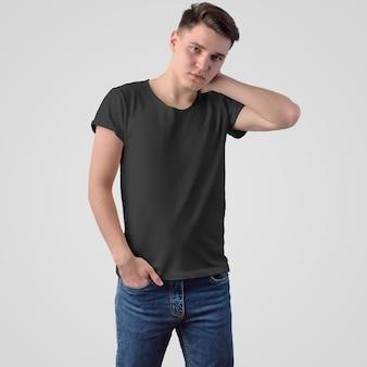 흰색 배경에 서 있는 얼굴에 청바지를 입은 젊은 남자의 검은색 티셔츠 템플릿. 온라인 상점에서 디자인 및 광고를 사용하기 위한 세련된 남성복 모형