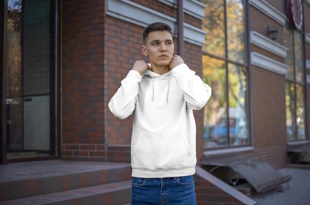 젊은 남자, 전면 보기에 흰색 까마귀의 템플릿. 거리에서 유행하는 옷을 선보입니다. 상점 광고용 모형 후드. 캐주얼 남성 의류를 디자인합니다.