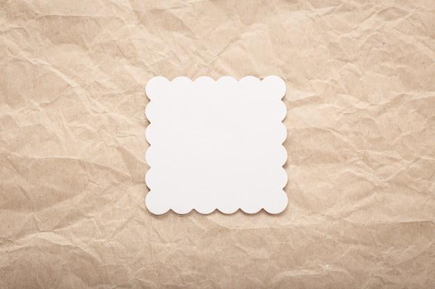 しわくちゃの紙の上の白い段ボールカードのテンプレート。用紙レイアウト