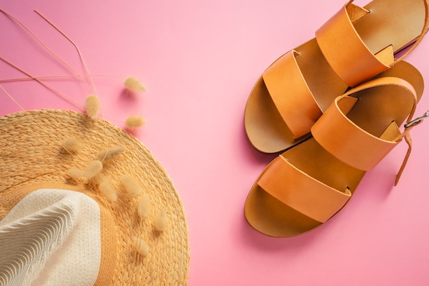 Template with brown leather sandals, straw hat and dried bunny tail grass on pink background. female accessories. summer travel vacation concept. sale kit. copy space.