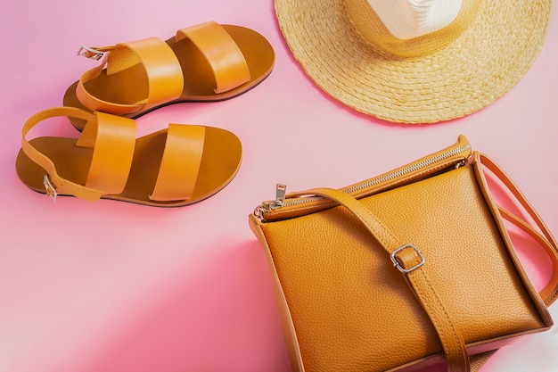 Template with brown leather sandals, straw hat and sand color bag on pink background. female accessories. summer travel vacation concept. sale kit. copy space.