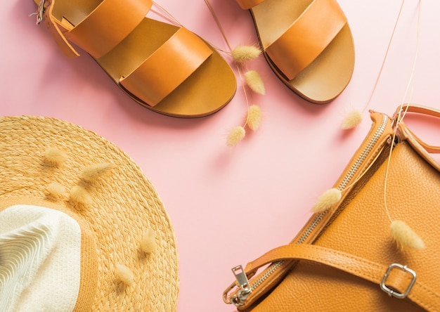 Template with brown leather sandals, straw hat and sand color bag with dried bunny tail grass isolated on pink background.