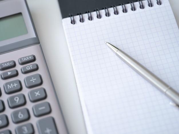 白いテーブルトップビューの背景に電卓ペンのメモ帳とテンプレート