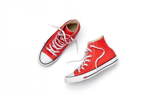 Шаблон с летней обувью на белом фоне. плоские лежал сверху красные кроссовки с копией пространства. концепция продажи модных покупок