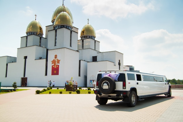 Temple, church with gold dome and wedding limousine