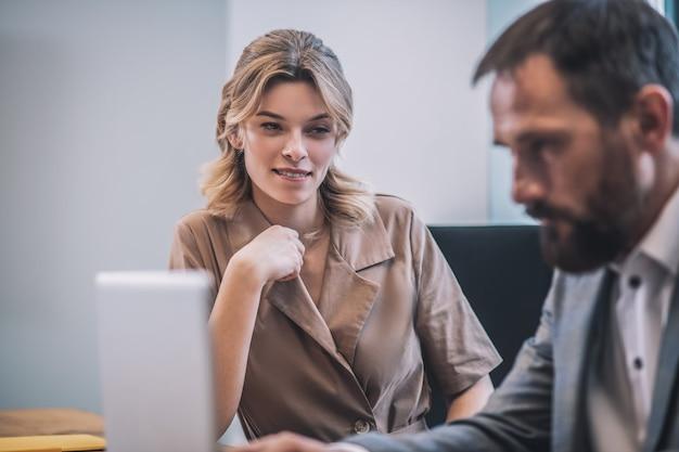 誘惑、同僚。ノートパソコンを注意深く見ている忙しい大人の上司の注目を集める若いブロンドの女性アシスタント