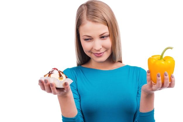 ダイエット中の誘惑。白い背景に立っている間、片手にサラダペッパーともう一方の手にケーキを持っている美しい若い女性