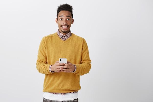 La tentazione tra due amanti aumenta. studente afroamericano attraente stupito ed elettrizzato in maglione giallo che tiene smartphone, legge un messaggio ed è stordito, pensando a cosa rispondere