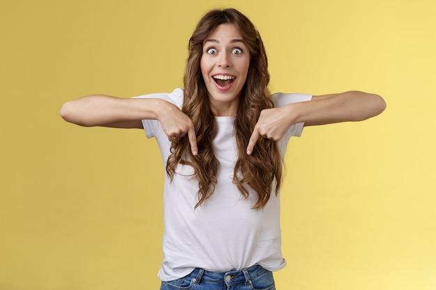 Заманчиво удивлен впечатлен возбужденная живая девушка фанатка ошеломленна проиграть речь очарованный указывая вниз взволнованный взгляд камера восхищение удивление полное недоверие стоять желтый фон