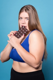 あなたを誘惑します。チョコレートを食べるセクシーな若い太りすぎの女性の肖像画。