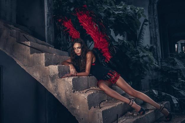 誘惑のコンセプトです。情熱的な顔の女性は役割ゲームをします。赤い翼を持つ黒いドレスの少女セクシーな悪魔、階段の上に横たわる欲望に満ちた悪魔
