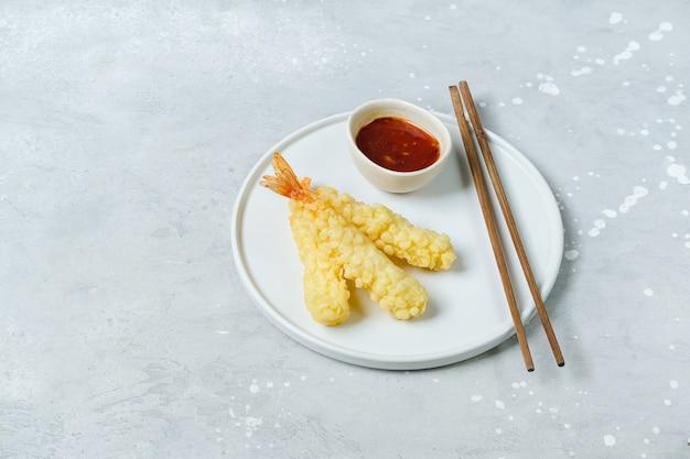 白い皿に甘いチリソースをのせた天ぷら海老。アジア料理のフードデリバリー