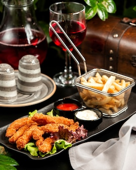 Tempura shrimps with french fries ketchup mayo and compote on table