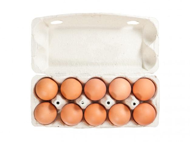 Десять коричневых яиц в открытой картонной упаковке, чтобы изолировать фон