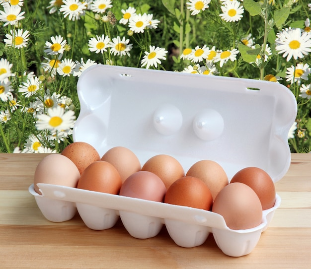 Ten chicken brown eggs in a white styrofoam package on the wooden table