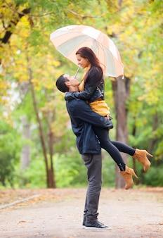 秋の公園で傘を持つ10のカップル