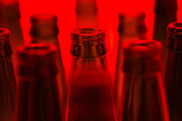10本の緑の空のビール瓶が赤い光で撃たれました。焦点が合っている1つの中央のボトル。
