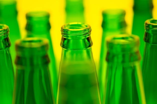 노란색 빛으로 총 10 개의 녹색 빈 맥주 병. 초점이 맞춰진 중앙 병 하나.