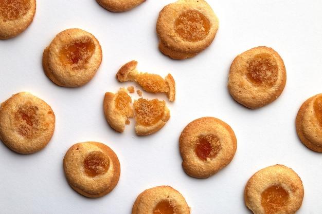 살구 잼을 곁들인 수제 쿠키 10 개가 비스듬히 균등하게 배열되어 있습니다. 흰색 배경에 고립
