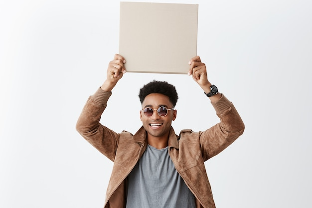 Ten out of ten. young good-looking dark-skinned stylish man with afro hairstyle in casual outfit holding cardboard over head, smiling with teeth. copy space