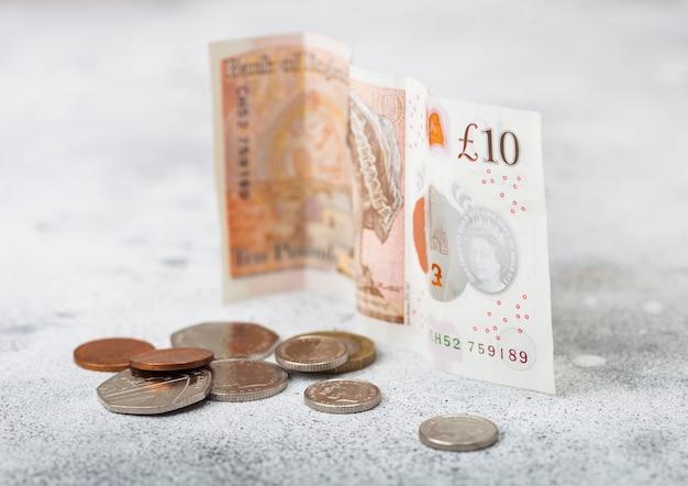 Банкнота в десять фунтов с монетой на светлой поверхности. концепция кризиса мировой экономики.