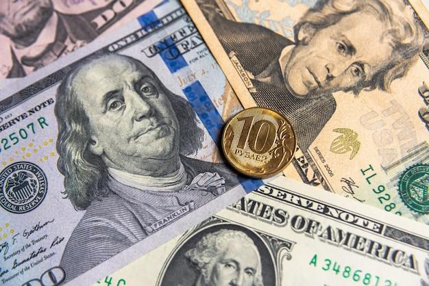 Монета десять российских рублей, лежащая на фоне доллара сша, девальвация национальной валюты