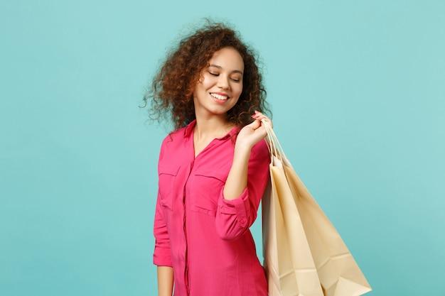 파란색 청록색 벽 배경에서 격리된 쇼핑 후 구매한 패키지 가방을 들고 분홍색 캐주얼 옷을 입은 부드러운 아프리카 소녀. 사람들은 진심 어린 감정 라이프 스타일 개념입니다. 복사 공간을 비웃습니다.