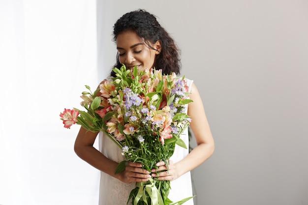 Mazzo sorridente della tenuta del fiorista africano tenero della donna di alstroemerias sopra la parete bianca. occhi chiusi.
