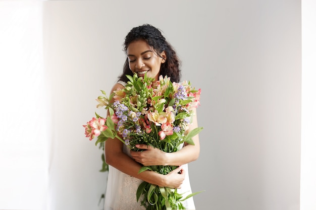 Tender african woman florist smiling holding bouquet of alstroemerias over white wall. closed eyes.