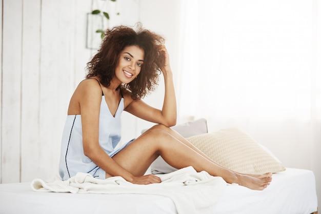 笑みを浮かべて自宅のベッドの上に座っているパジャマで優しいアフリカ女性。