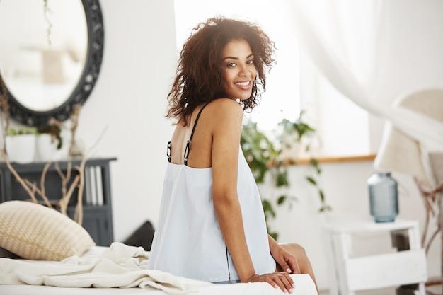 Нежная африканская женщина в одежде для сна сидя на кровати дома усмехаясь.
